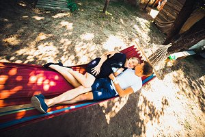 Pregnant woman and husband, resting in a hammock
