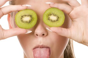 woman with two slices of kiwi
