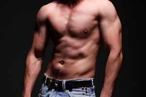 man in jeans showing his abs