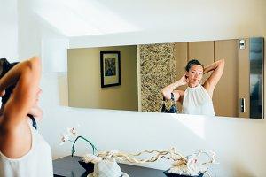 Woman retouching hotel hall mirror