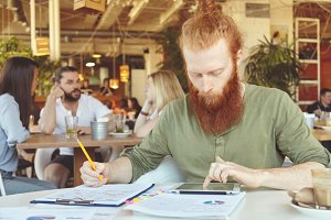 Bearded student working on course paper, making research, analyzing statistics on tablet, writing down in notebook using pencil. Redhead entrepreneur sitting at cafe with touch pad during lunch break