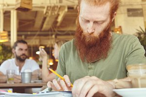 Young serious freelancer working distantly, using touch pad pc, sitting at cafe, holding pencil and making notes. Redhead student preparing for lesson at university, browsing Internet, looking concentrated