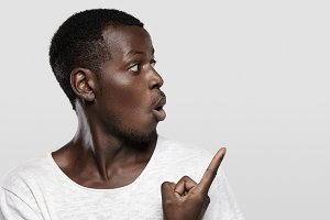 """Attractive young dark-skinned customer or employee looking surprised or shocked, pointing his finger at white studio wall with copy space for your advertising content, saying 'Look at that!"""""""