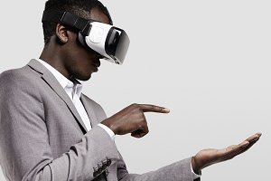 Dark-skinned man in formal wear with virtual reality headset for smart phone on his head, playing video games., holding his hands as if typing message on electronic device, looking concentrated