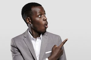 Advertising concept. Portrait of handsome African entrepreneur or office worker wearing suit pointing his finger at white studio wall with copy space for your content, looking shocked and surprised