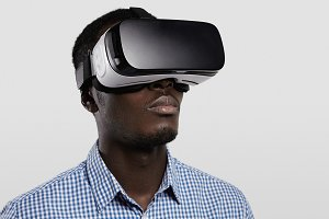 Technology, entertainment, gaming, cyberspace and people concept. Serious dark-skinned player wearing checkered shirt and big modern 3-D glasses. Black man playing video game with VR headset