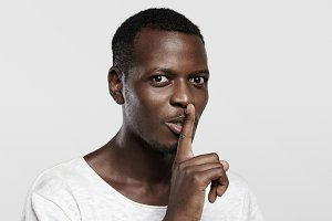 Body language. Young African man in white t-shirt holding finger on his lips, asking to keep silence about confidential information, saying 'shh', looking at camera with serious face expression