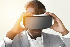 Technology, entertainment, gaming, cyberspace and people concept. Young African man wearing formal suit and big 3-D glasses, holding virtual reality headset with both hands, while playing video game