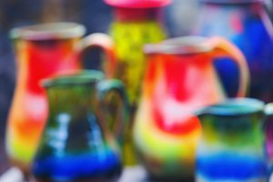 Colorful clay pots for water. Blurry