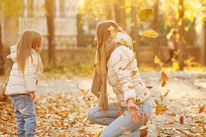 Mother and daughter toss up leaves