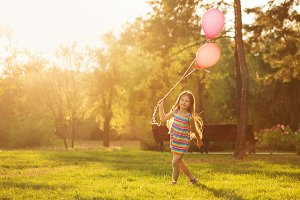 Little girl walks with balloons