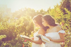 Two sisters reading books