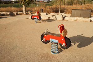 Red toy motorcycles in a playground