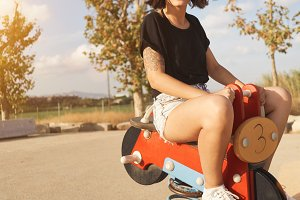 Young woman riding a toy motorcycle in  playground