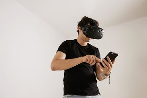 Man in VR glasses looking at his smartphone