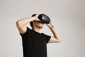 Model in blank black t-shirt putting on VR glasses