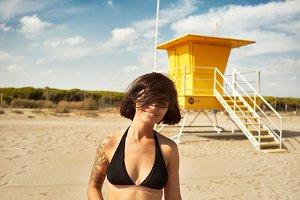 Young woman in black bikini near a yellow lifeguard post