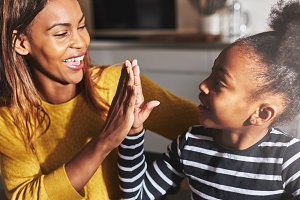 Black mother and child high five