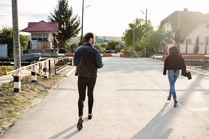 man and woman running to the railroad crossing