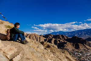 Young Asian traveler sitting on high hills and looking away at the village over blue sky background in Leh, Ladakh, India