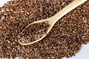 flax seed with spoon isolated on white background