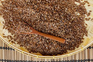 flax seed with spoon placed on flat woven basket