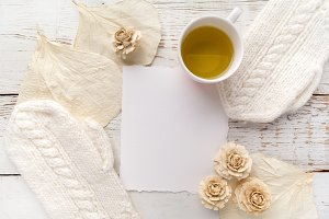 Cup of tea with gloves, flowers and blank card on white wooden background