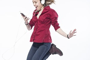Happy girl jumping with headphones
