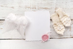 New Born or baptism Greeting Card. Blank with baby girl gloves and angel wings on white wooden background