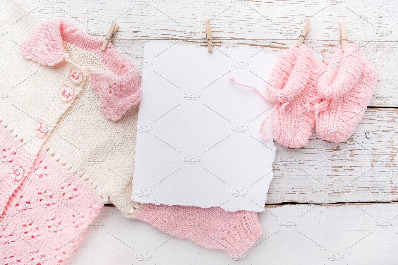 Baby girl clothes with blank card on white wooden ...