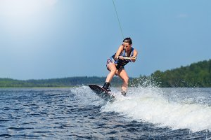 Slim brunette woman riding wakeboard on motorboat wave in lake