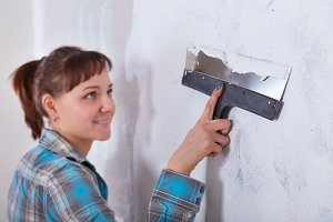 house improvement. woman worker puts stucco on wall