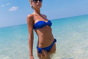Slim blonde woman swimming in clear water on tropic beach