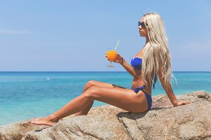 Slim blonde long haired woman in bikini on tropical beach