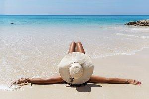 slim brunette woman in hat sunslasses sunbathe on the beach