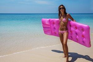 Young slim brunette woman in sunglasses sunbathe on tropical beach