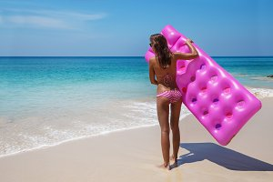 Young slim woman sunbath with air mattress on tropic beach