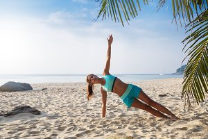 woman practise yoga pose on beach