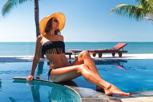 beautiful young slim woman in straw hat and sunglasses sunbath