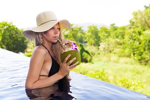 woman in hat drinks healthy detox coconut juice