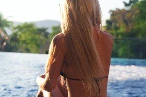 Pretty slim blonde woman gets suntan near swimming pool