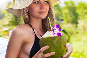 Young slim blonde woman hat drinks healthy coconut juice