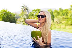 blonde woman with coconut in pool