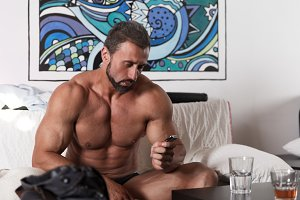Handsome muscle man with hangover look on watch morning