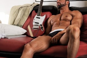 Handsome muscle man hangover guitar
