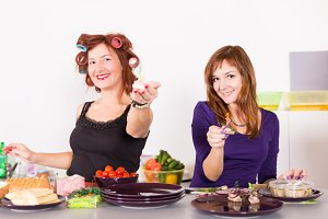 Two young pretty woman housewife cooking with curlers hair