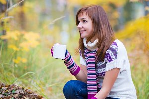Pretty woman with tea cup in autumn park