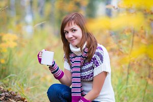 Pretty woman in an autumn park with cup