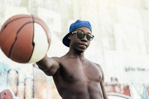 Black Man holding a basket ball.