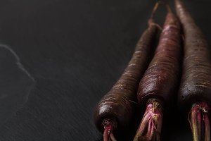 Ripe black carrots. Dark stone background. Autumn harvest. Top view